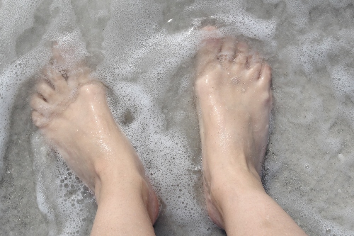 A person's feet soak in a freshly cleaned walk-in bathtub.