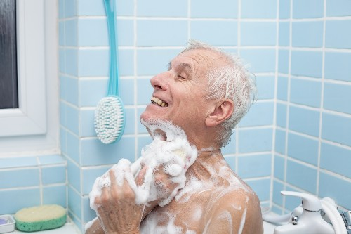 An elderly man smiles while washing up in a bathtub.