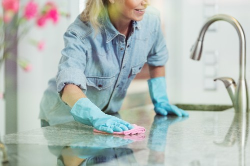 A woman uses countertop cleaning tips to safely protect her kitchen counters.